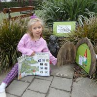 Poppy at the Botanical Gardens with her gnome-finding map ready to start the treasure hunt
