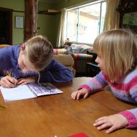 Poppy helping Mahalia write a story about mustering